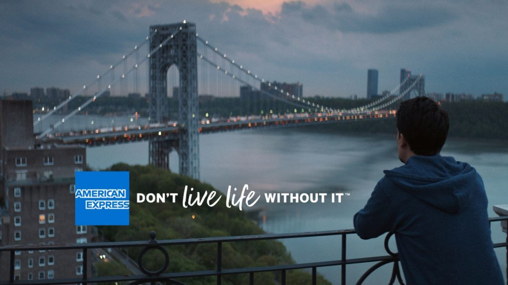 American Express ad: Man looks at a bridge from his balcony.