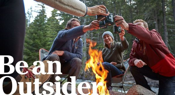 """LL Bean """"Be an Outsider"""" ad: Campmates raise their mugs over a campfire in the woods."""