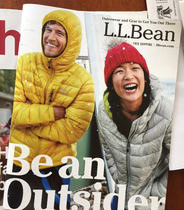 A man and a woman dressed in outerwear have a laugh on the cover of an LL Bean catalog.