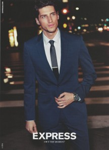Express Ad: Handsome man in a suit crosses a city street at night.
