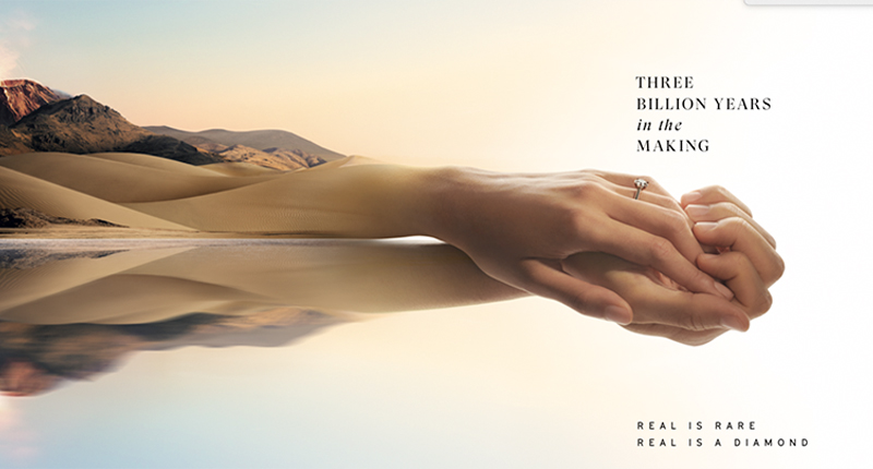 """Diamond Ad: Interlocked hands emerge from mountains and dunes with the caption """"Three Billion Years in the Making."""""""