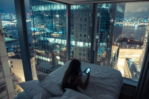 Girl alone in her big-city apartment looks at her phone.